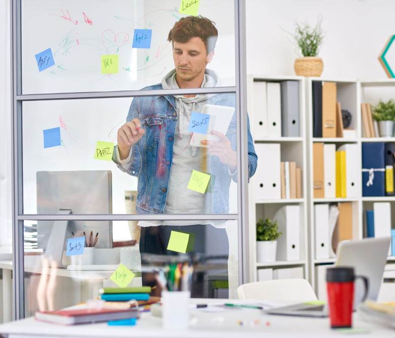 Young startup entrepreneur placing idea notes on interior glass window